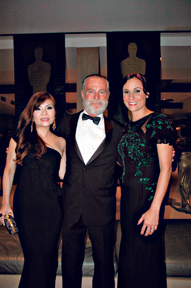 HIFF executive director Chuck Boller (center) with event chairwomen Kristen Chan and Nicole Kobayashi.