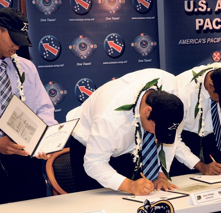 """Maj. Gen. Joseph Chaves, deputy commander, U.S. Army Pacific, leads new cadets Shaun Kagawa, Jaryn Villegas and Paul-Andrew Rhoden in a cheer of """"Go Army, Beat Navy"""" during the West Point football signing ceremony at Fort Shafter."""