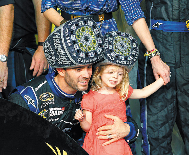 The hats may look silly, but Jimmie Johnson (with daughter Genevieve) is part of sport's greatest dynasty. AP photo