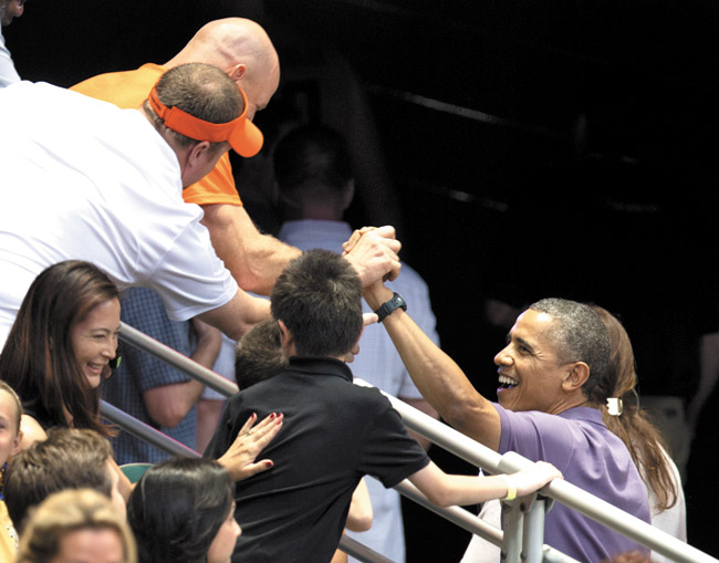 President Barack Obama greets people in the stands Dec. 22 as he takes a break from watching the Oregon State University versus University of Akron college basketball game at the Diamond Head Classic at Stan Sheriff Center. AP photo/Carolyn Kaster