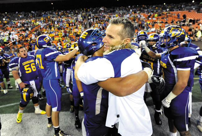 Kaiser High coach Rich Miano hugs Parker Higgins as the team celebrates at the end of the Cougars' OIA DII championship win over Pearl City at Aloha Stadium. The celebration was repeated a few weeks later when Kaiser defeated Kauai for the state title