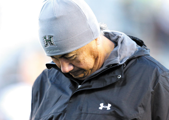 A dejected Norm Chow bows his head after a 56-59 loss to Wyoming. UH is banking on Chow to turn things around in 2014 and hoping fans will be there to see it | AP photo
