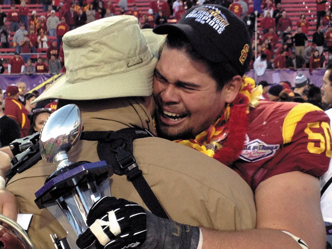 Tearful Trojan Abe Markowitz hugs dad Barry following the USC vs. Fresno State Las Vegas Bowl after winning the prestigious Outperformer Award | Mike Enzenbacher photo
