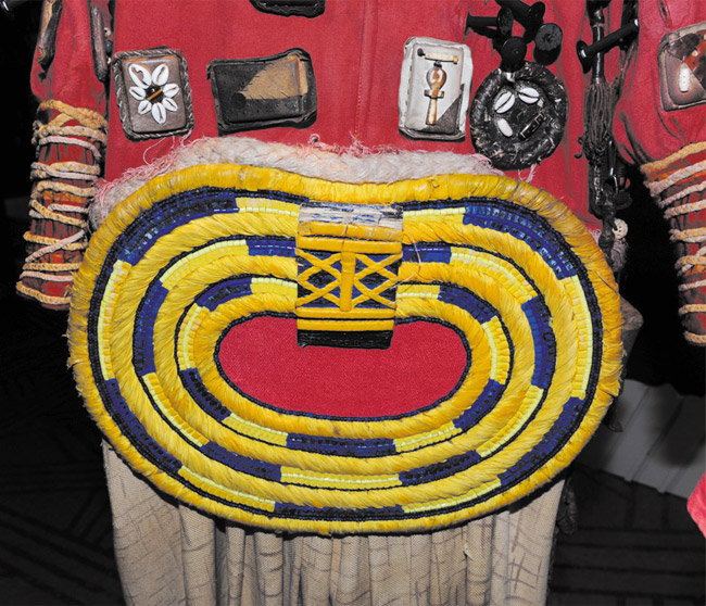 Wardrobe supervisor Gregory Young holds Rafiki's costume. It features a linen fabric decorated with various wooden beads, glass beads, feathers, cowrie shells, leather patches and human hair on the collar