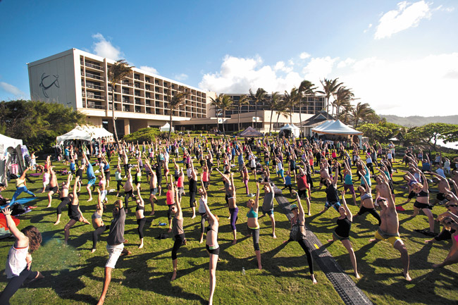Kahuku's Turtle Bay Resort will come alive at this year's Wanderlust Yoga Festival with dozens of healthy, fun activities, workshops and adventures, all planned for Feb. 27-March 2. A mass exercise at the resort for last year's Wanderlust Hawaii fans - all with their backs to the morning sun (above) - was a hit. Some sessions and packages still may be available for next week's celebration of health and fitness. Photo by Ali Kaukas.