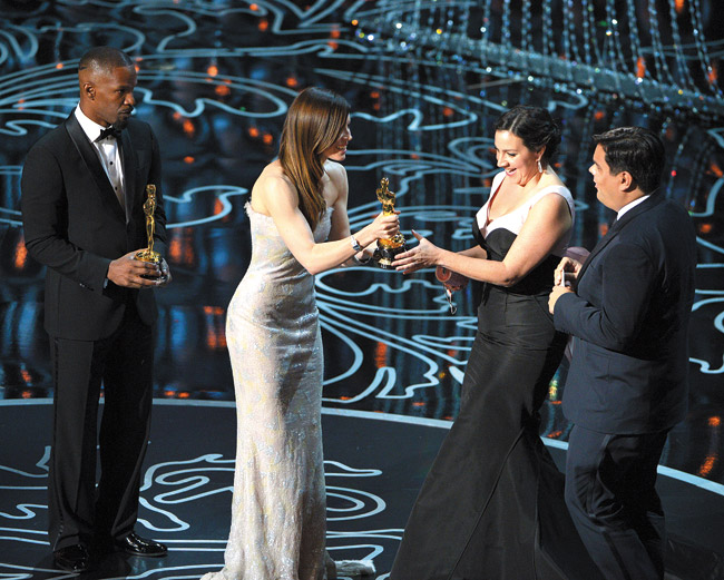 Jamie Foxx (from left) and Jessica Biel present Kristen Anderson-Lopez and Robert Lopez with the award for an original song in a feature film for 'Let It Go' from 'Frozen' during the Oscars March 2 | John Shearer/Invision/AP