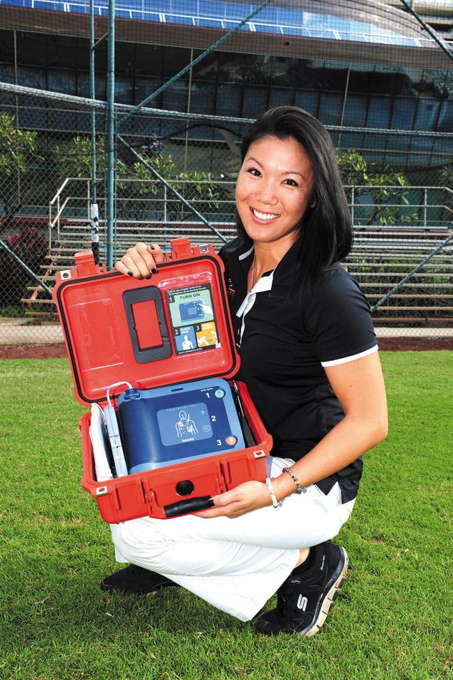 Iolani School athletic trainer Louise Inafuku with an automated external defibrillator | Nathalie Walker photo