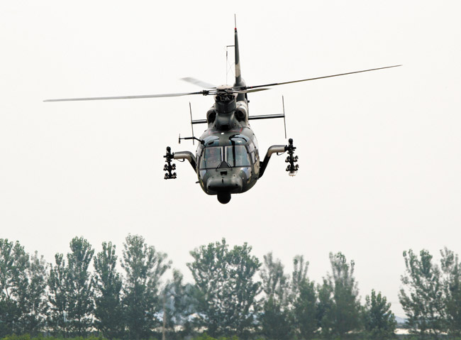 A Chinese Army Z-9WZ attack helicopter, designed and manufactured by China, performs a flight demonstration for press at a base of Chinese People's Liberation Army, Army Aviation 4th Helicopter Regiment | AP photo/Andy Wong