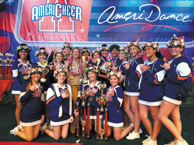 Kalaheo High School cheerleading coach Shannon Callen (center, with lei) and her national champion cheerleading team and trophies, following their triumphant performance at the Orlando, Fla., competition. Photo from Shannon Callen.
