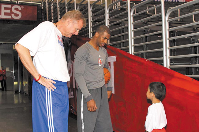Dave Severns, director of player development, L.A. Clippers, and Clippers guard Chris Paul talk with a young basketball camper. Photo courtesy Byron Mello