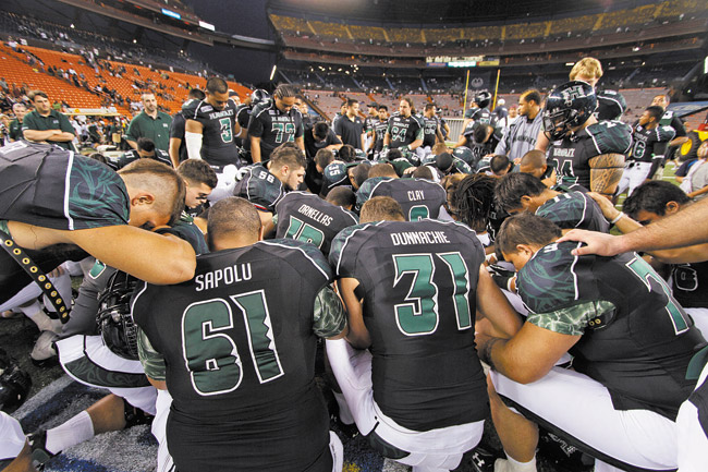 UH players pray after losing to BYU in 2011 | Dennis Oda / Star-Advertiser photo
