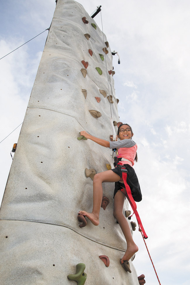 Caitlyn Malalis looks down from the rock tower she is climbing during the Pride for Ewa fair April 26 at Hoalauna Park. Photo by Anthony Consillio, aconsillio@midweek.com.