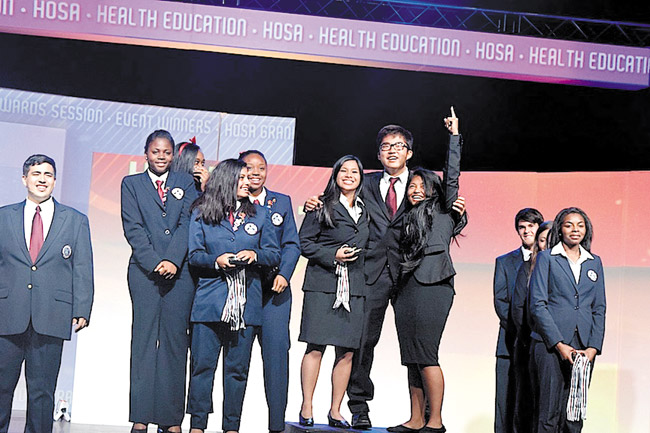 Rejoicing national champions from Mililani High School's delegation to the recent HOSA-Future Health Professionals' conference in Orlando are (from left, group with No. 1 salute) Fejiereich Luz Lopez, Mason Matsuo and Chasidee delaCuesta-Batara. Photo from Candace Chun.