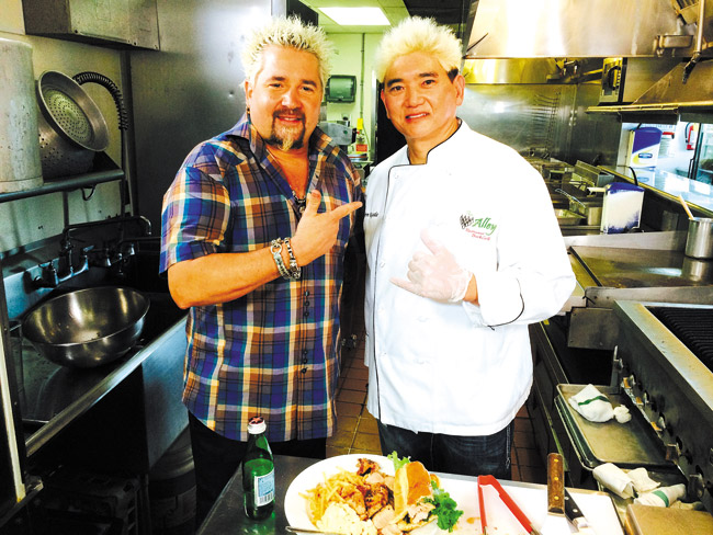TV host Guy Fieri (left) and The Alley Restaurant chef/co-owner Glenn Uyeda ham it up at the popular Aiea bowling alley eatery. Photo by Brandon Agtarap.