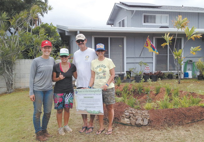 The Gomes family home in Enchanted Lake now has its own rain garden, with these proud installers standing by its side: (from left) Hui o Ko'olaupoko project coordinator Annie Lovell, and homeowners Maria, Paul and Lorna Gomes. Photo from Annie Lovell.