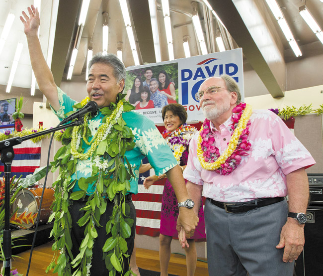 State Sen. David Ige (left) waves to his supporters and thanks Gov. Neil Abercrombie Aug. 9 after Ige defeated the governor in the primary election. AP PHOTO/EUGENE TANNER
