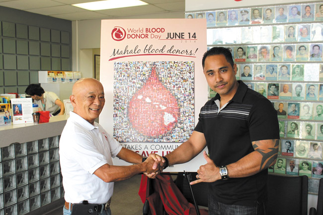 Veteran donor and Waipahu resident Francis Nagata (left) with new super donor (56 pints or more) Dustin Guillermo in front of the World Blood Donor mosaic at Blood Bank of Hawaii's Dillingham Boulevard headquarters. Photo from Vanessa-Helen Sim.